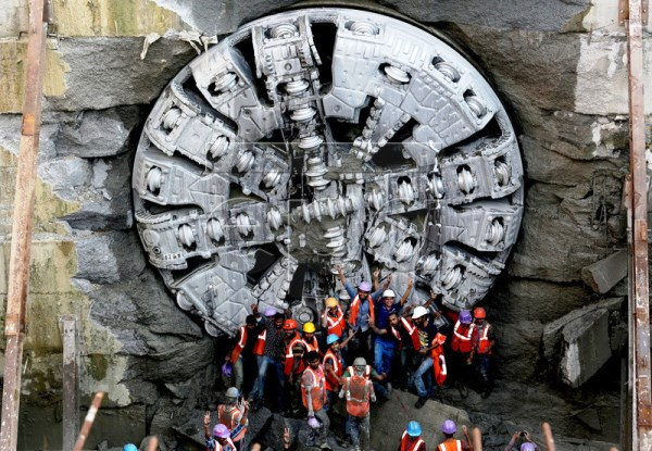 Workers pose for photos in front of Krishna - Photo Copyright: European Pressphoto Agency