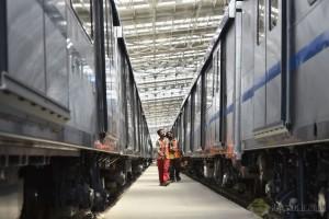 Workers walk along 2 trains - Photo Copyright ProKerala
